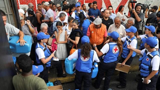 Foto: Trabajadores de Cruz Roja Venezolana reparten agua y píldoras de purificación en el barrio de Agua Salud, en Caracas. El 16 de abril de 2019