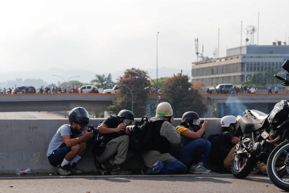 Periodistas y miembros de los medios de comunicación toman resguardo frente a la base militar 'La Carlota' (Reuters)