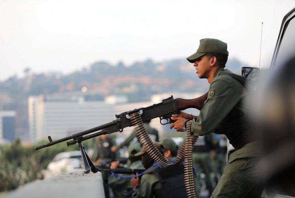 Un militar apunta una ametralladora hacia la base aérea Generalísimo Francisco Miranda 'La Carlota' en Caracas (Reuters)