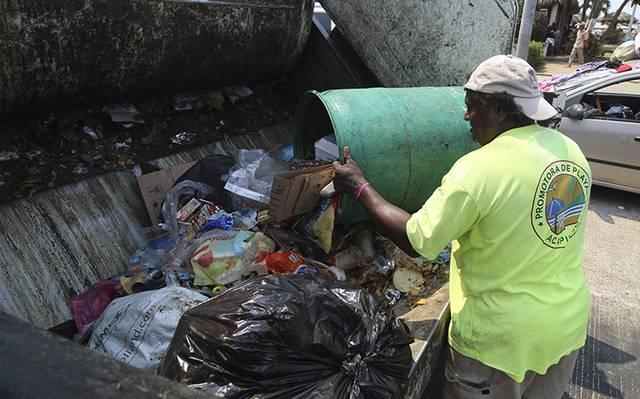 Un recolector de basura y trabajador de la Promotora y Administradora de Playas de Acapulco vuelca un bote de basura en un camión (El Sol de México)