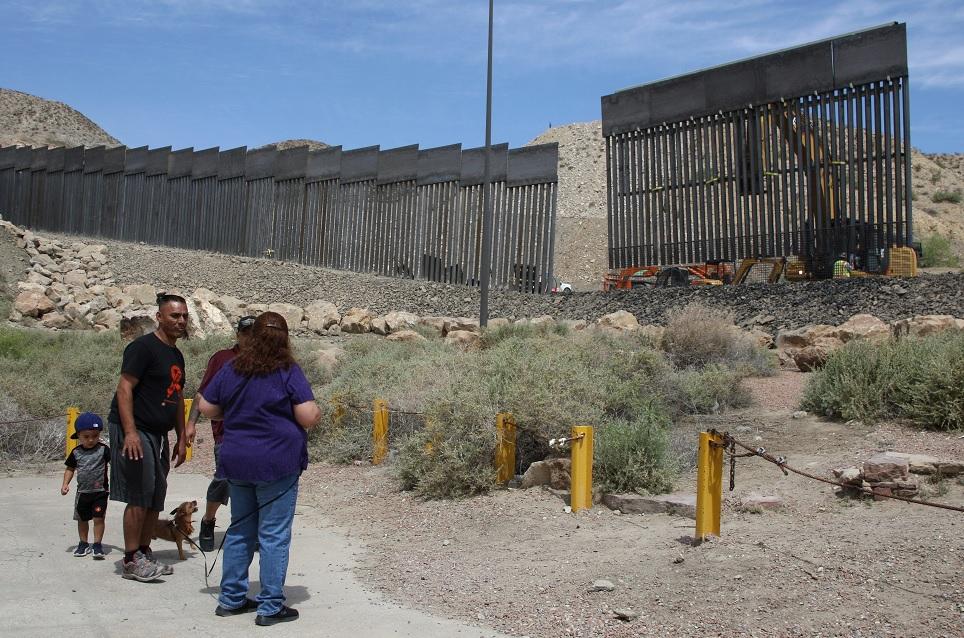 Foto: Varias personas observan la construcción de un muro fronterizo. El 27 de mayo de 2019