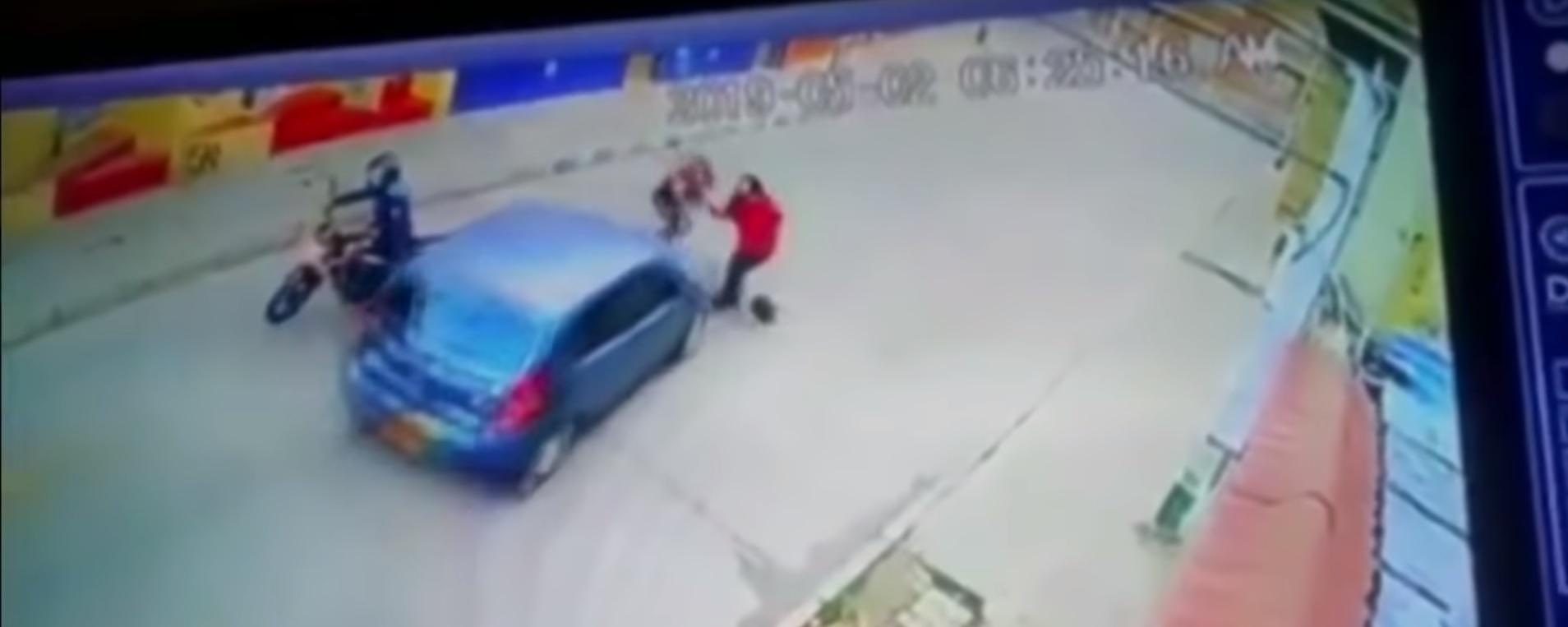 Momento en el que el automovil azul toma la desición de embestir a la ladrona para alejarla de su víctima (Noticias Caracol Captura de Pantalla)