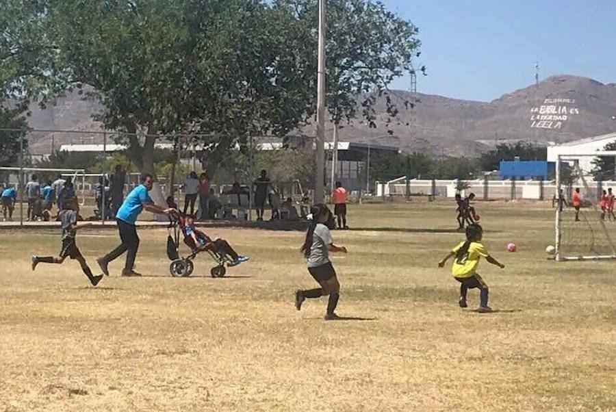 Foto Padre empuja la silla de ruedas de su hijo para que pueda jugar futbol 29 mayo 2019
