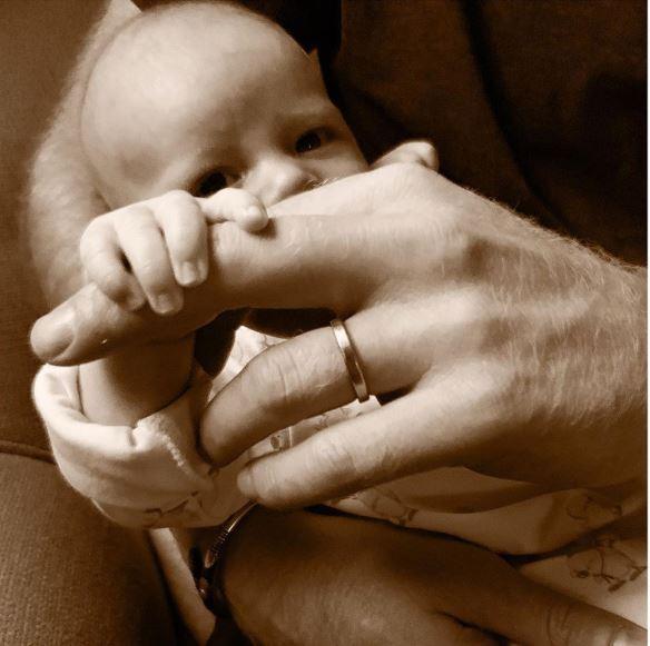 Foto: En la imagen se ve al niño recostado en el regazo del príncipe, al que le agarra el dedo corazón de la mano izquierda, 16 junio 2019