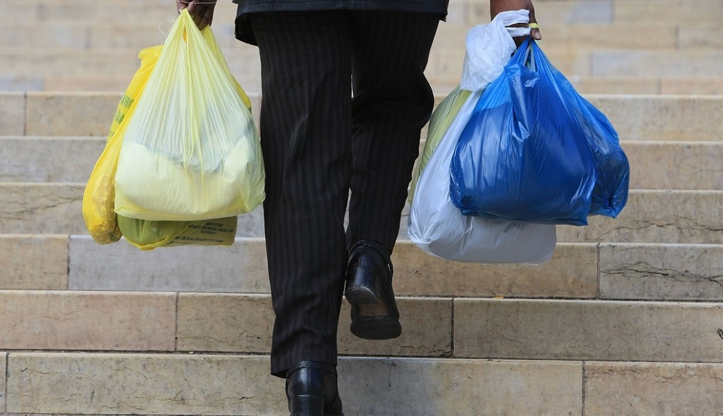 Foto: Un hombre sube escaleras cargando varias bolsas de plástico. El 4 de marzo de 2018