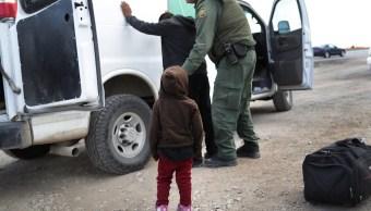 Foto: Un niño observa mientras un agente fronterizo de EEUU registra a un compañero migrante. El 1 de febrero de 2019