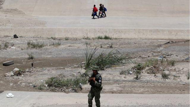 Foto: Un miembro de la Guardia Nacional de México vigila mientras una familia migrante camina por la orilla del Río Bravo después de cruzar ilegalmente hacia Estados Unidos. El 25 de junio de 2019