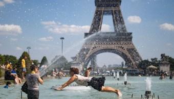 Foto: Una mujer se refresca en el agua de la fuente de la Plaza del Trocadero, frente a la Torre Eiffel, en París, Francia. El 25 de junio de 2019