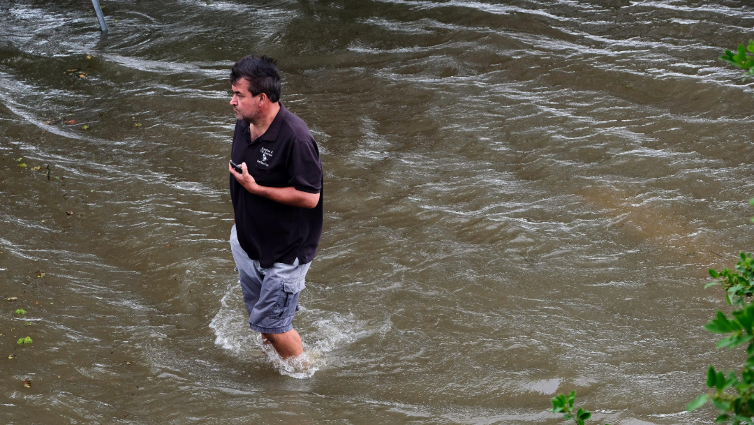 fOTO: Un sujeto camina a través de un área inundada cerca del lago Pontchartrain en Mandeville, Louisiana, 13 julio 2019