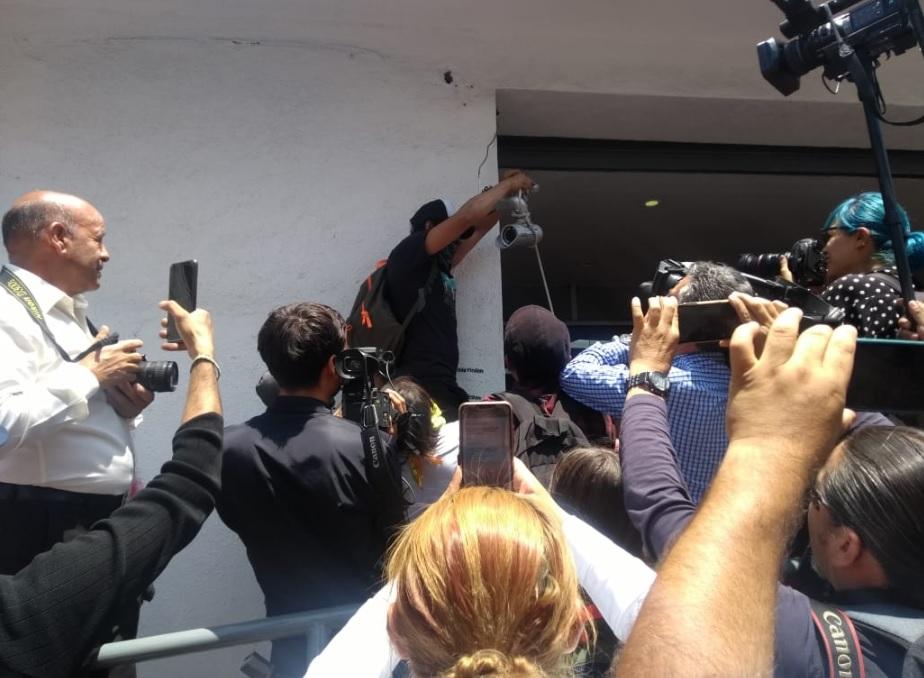 Hombre con el rostro cubierto arranca una cámara de seguridad