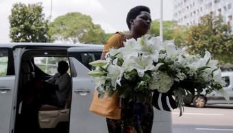 Foto: Una mujer lleva una corona de flores al ataúd donde descansa el cuerpo del expresidente de Zimbabwe Robert Mugabe, 7 septiembre 2019