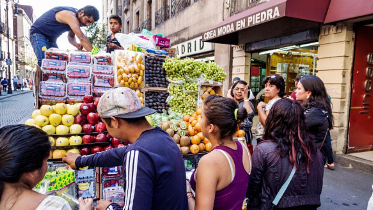 Foto: Varias personas comprar fruta a un vendedor ambulante en la zona Centro de la Ciudad de México. Getty Images