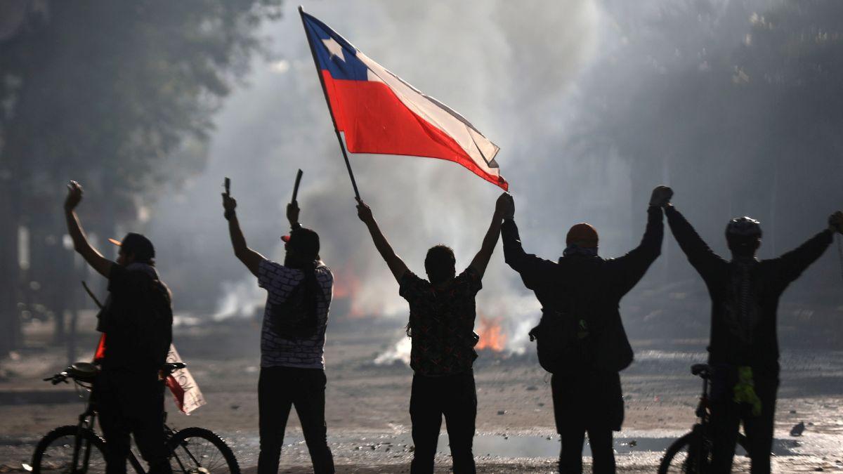 Foto: Manifestantes ondean una bandera de Chile en las calles de Santiago. Reuters