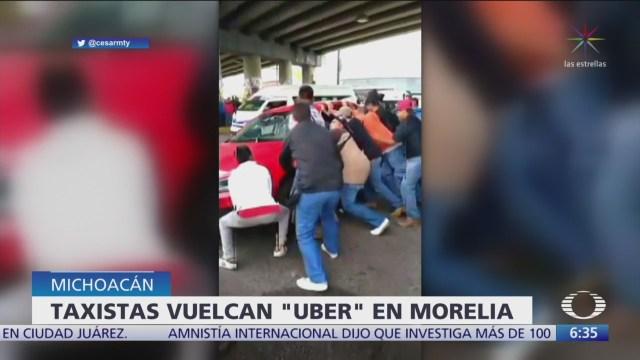 Taxistas voltean auto particular al que confundieron con Uber