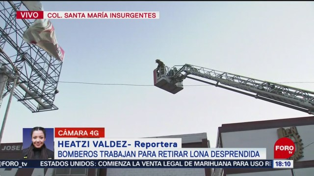 FOTO: 1 enero 2020, bomberos trabajan para retirar lona rasgada por fuerte viento en cdmx