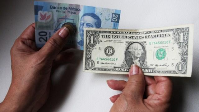 Foto: Una persona sostiene en su mano izquierda un billete de veinte pesos mexicanos y en la derecha un dólar, 8 enero 2020