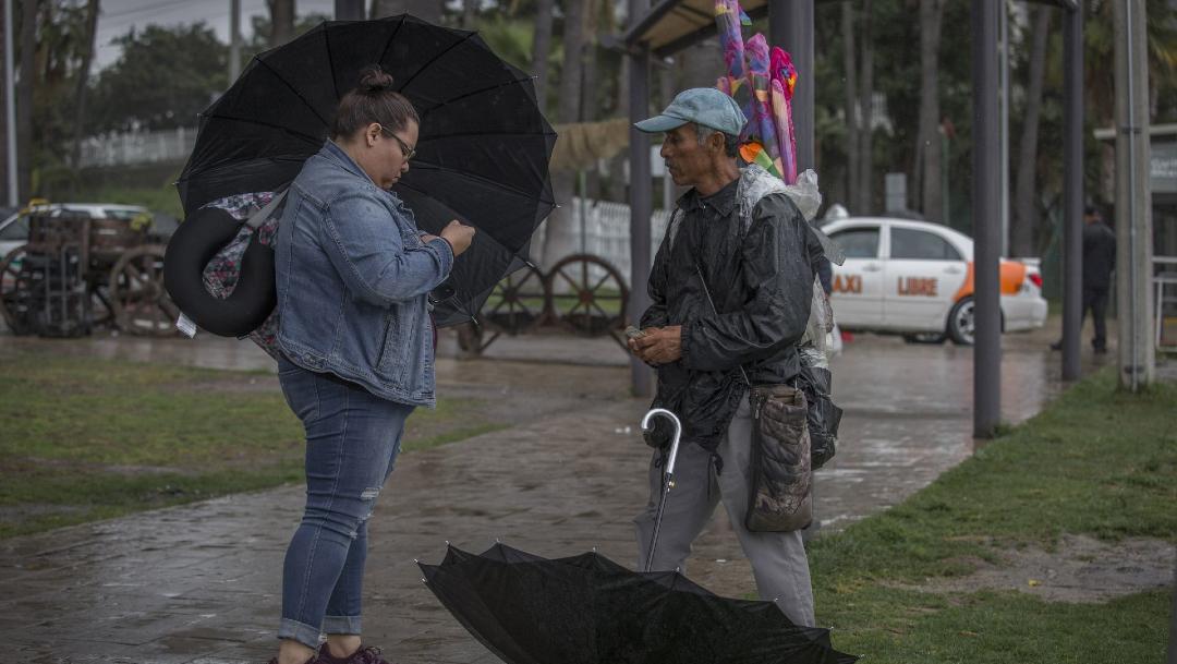 Dos personas se cubren de la lluvia que se registra en algunos estados del país. (Foto: cuartoscuro)