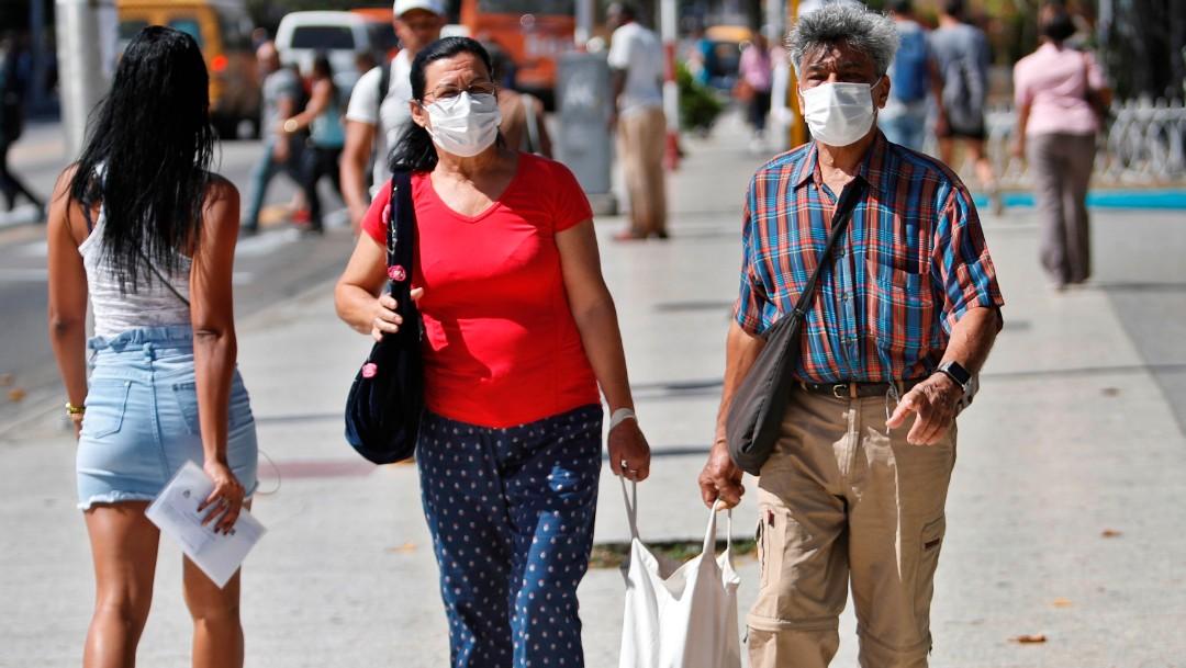Foto: Una pareja de cubanos camina por La Habana usando cubreboca. Efe