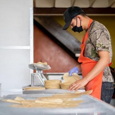 Foto: Un joven hace tortillas usando cubreboca. Getty Images