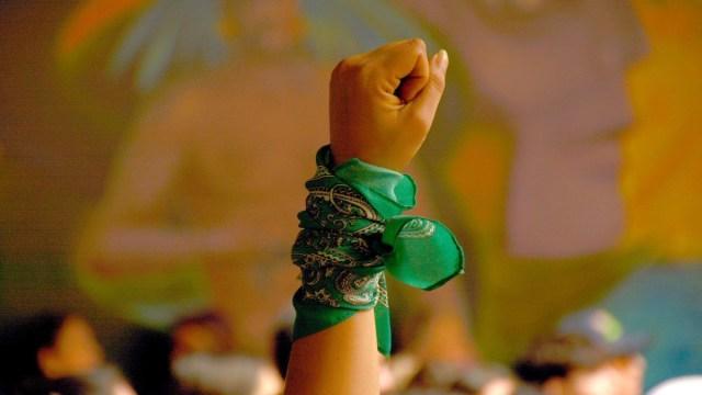 Foto: Una mujer alza el puño con una pañoleta verde. Cuartoscuro