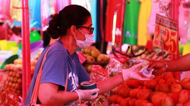 Foto: Una señora usa guantes y cubreboca durante sus compras en un mercado de la Ciudad de México. Getty Images