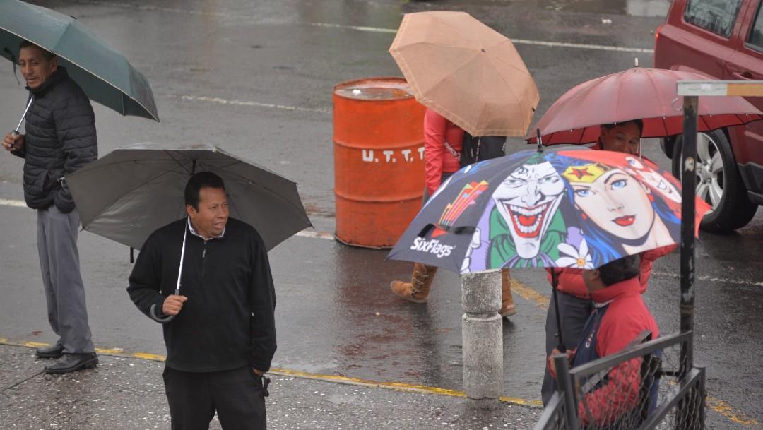 Foto: Un grupo de personas se protege de la lluvia, 15 marzo 2020