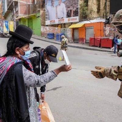 Foto: Mujeres y militares usan cubrebocas en calles de Bolivia. Getty Images