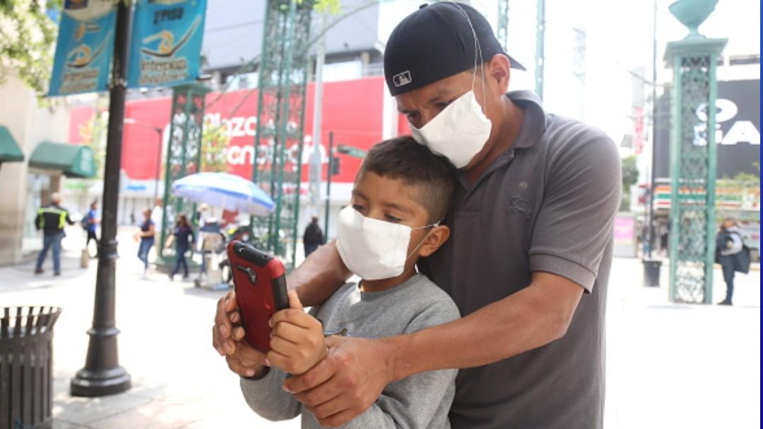Foto: Un padre y su hijo usan cubrebocas en calles de la CDMX. Getty Images