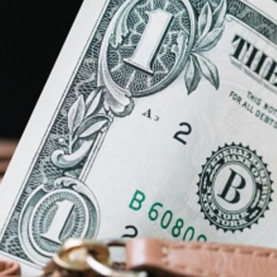 Una mujer saca de su cartera un billete de un dólar. Getty Images/Archivo