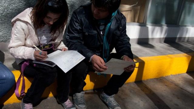 Un par de jóvenes en busca de trabajo llenan una solicitud de empleo. (Foto: Cuartoscuro)