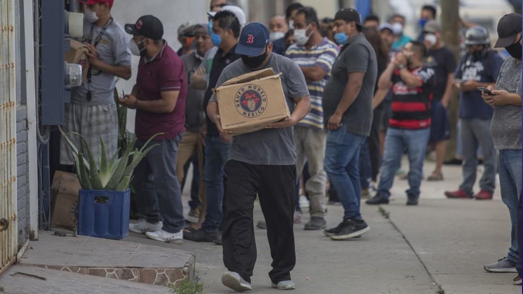 Decenas de hombres hacen fila para comprar cerveza. Cuartoscuro