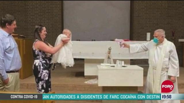 sacerdote usa pistola de agua para bautizar a un bebe