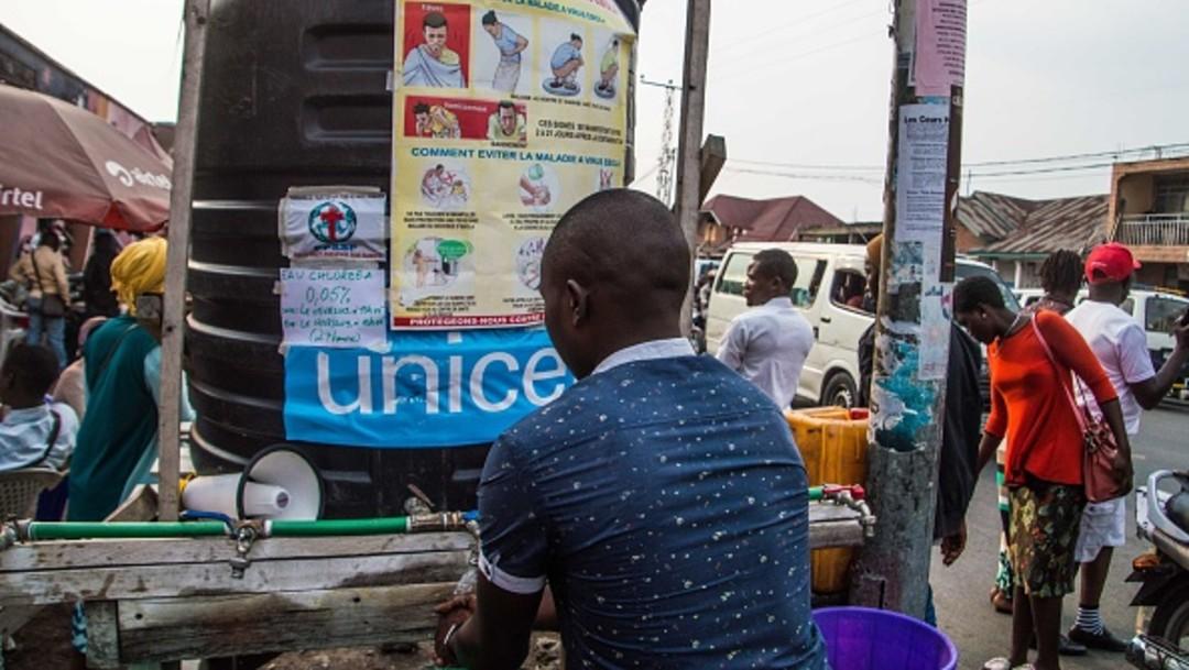 Hombre frente a letrero de medidas contra ébola en Congo, África