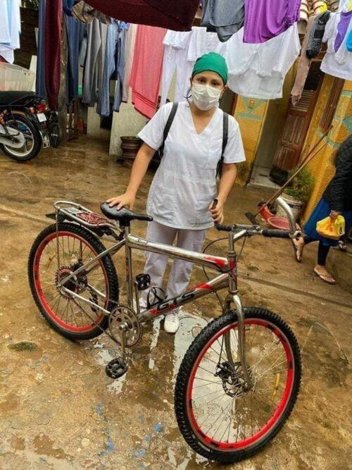 Foto de enfermera en Bolivia con bicicleta en inundación