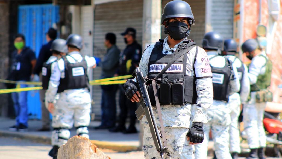 Elementos de la Guardia Nacional resguardan la zona donde fue hallado el cuerpo de una persona en un taller eléctrico en Jiutepec. (Foto: EFE)