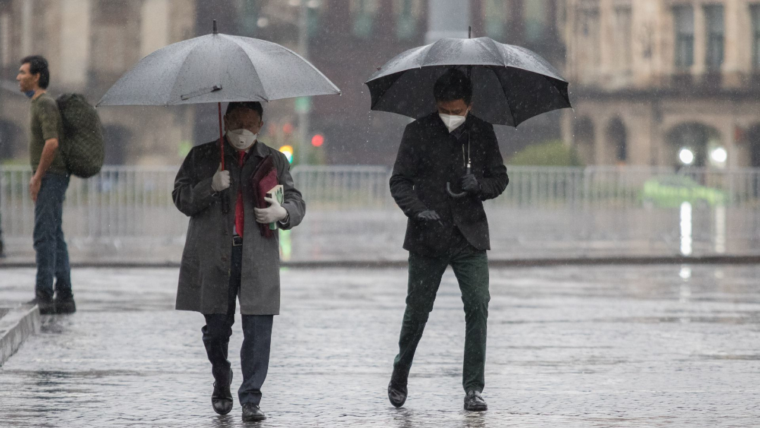 Dos personas se protegen de la lluvia bajo un paraguas en la Ciudad de México.