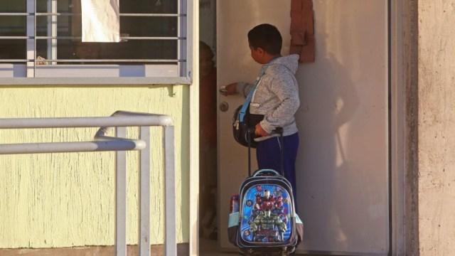 Un niño pide permiso para entrar al salón de clases. Cuartoscuro