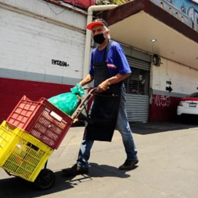 """Un señor empuja un """"diablo"""" con cajas con comida en un mercado de CDMX. Getty Images"""