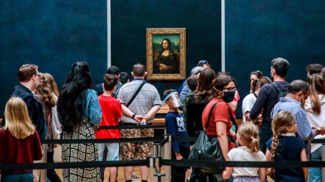 Gente apreciando a La Mona Lisa, en el Museo del Louvre