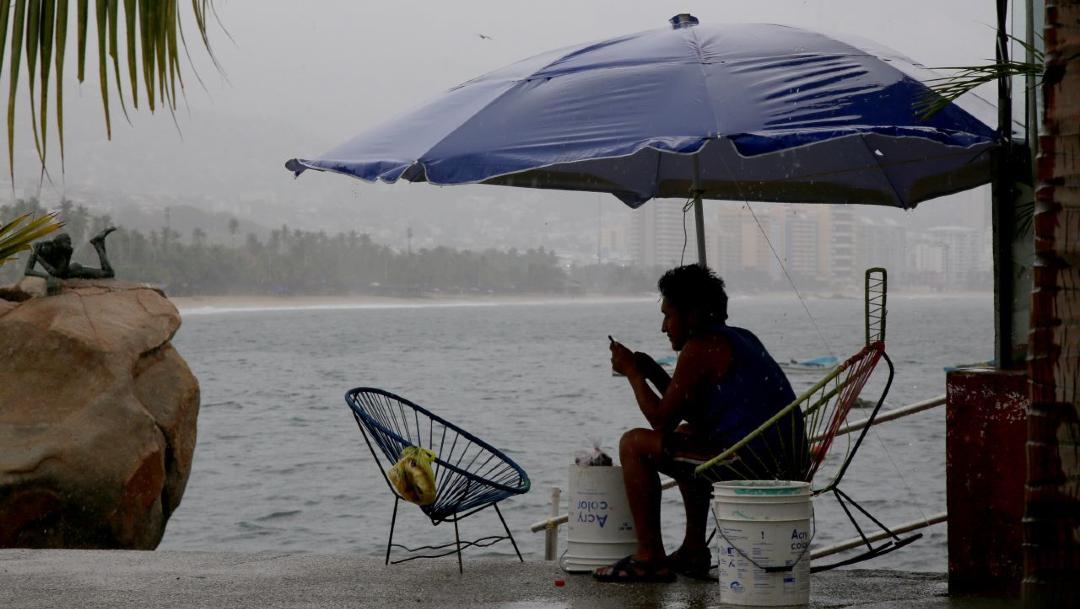 Un joven se resguarda bajo paragüas de la lluvia, frente al mar