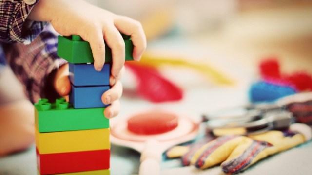 Mano niño jugando con bloques de colores para nota sobre niño curado de cáncer