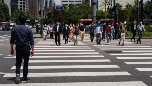 Personas caminando en calle de Seú; Corea del Sur afronta segunda oleada de coronavirus