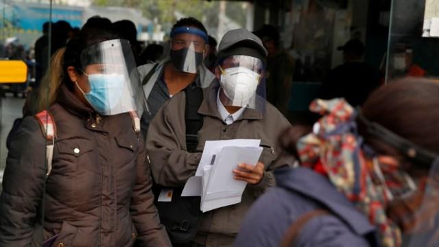 Personas con cubrebocas y caretas en Perú
