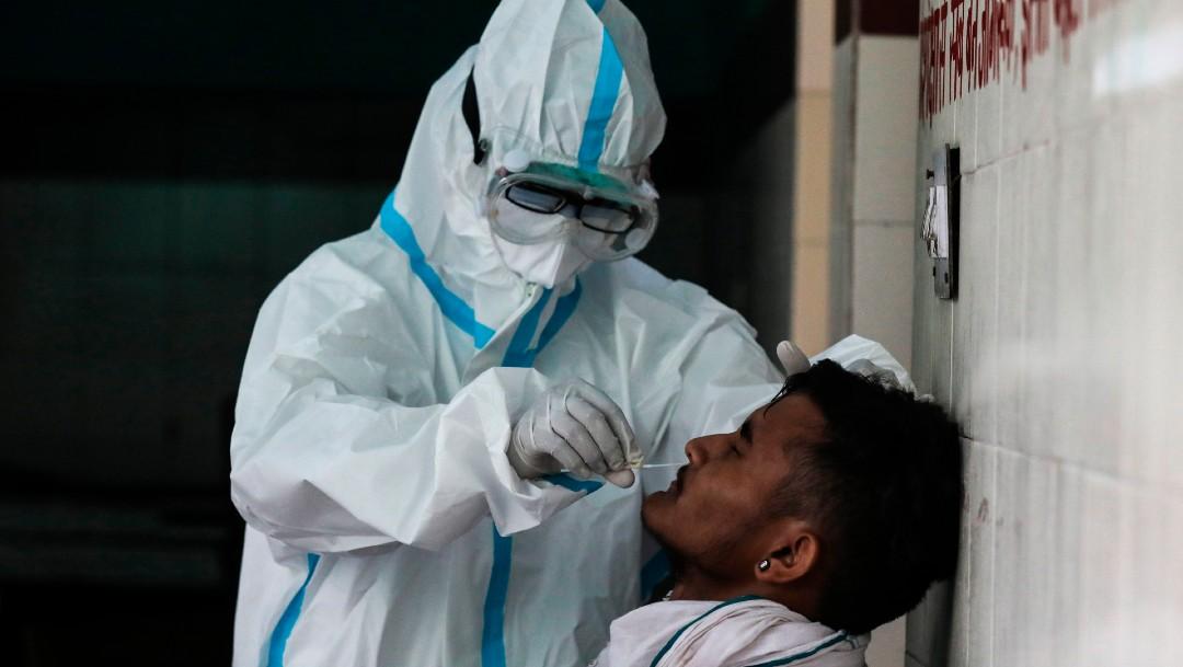 Un trabajador de salud toma muestra de coronavirus a hombre en India