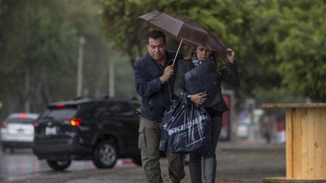 Dos personas se protegen de la lluvia