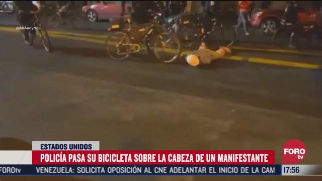 policia pasa su bicicleta sobre la cabeza de un manifestante