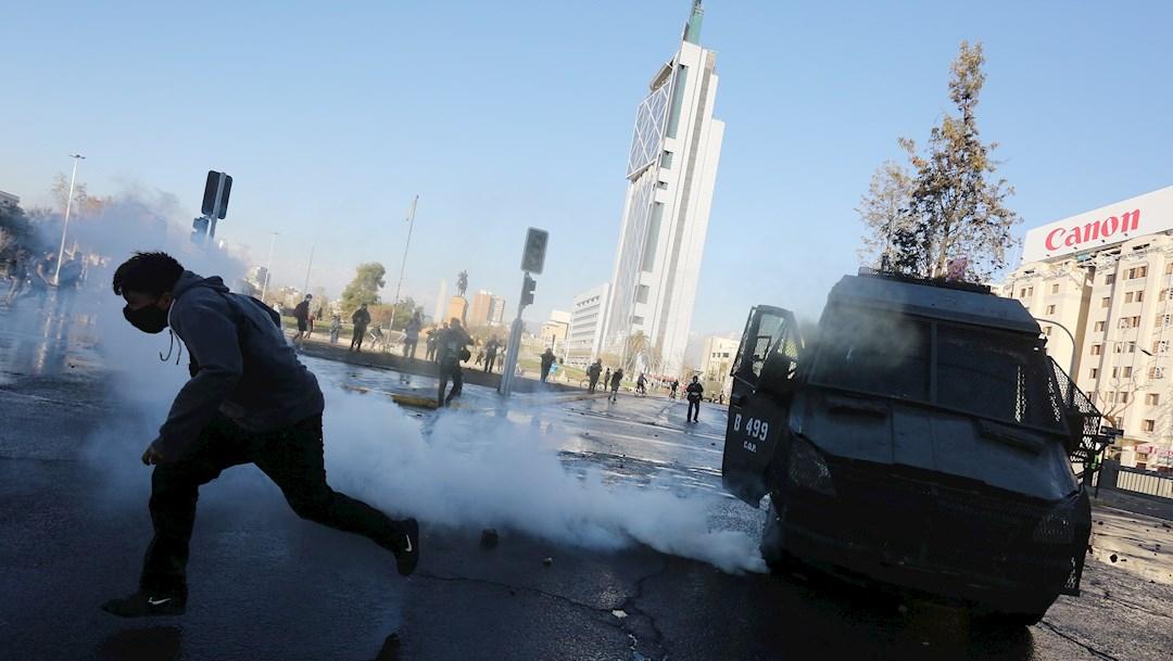 Un hombre corre del gas durante una protesta por la conmemoración del 47ª aniversario del golpe de Estado e inicio de la dictadura en Chile