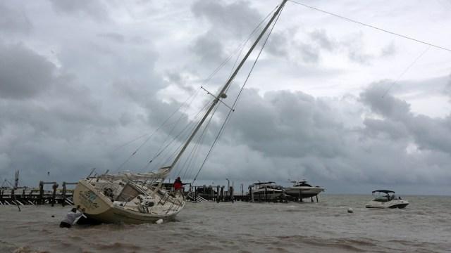 Un hombre empuja una embarcación encallada en una playa por los fuertes vientos de la tormenta tropical Gamma en Cancún