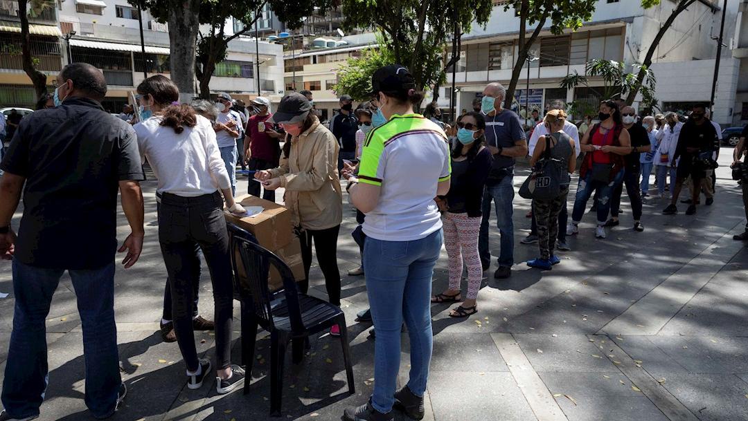 Personas hacen fila para votar en la consulta popular impulsada por el opositor Juan Guaidó en Caracas. Venezuela