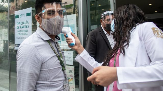 Personal médico le toma la temperatura a una persona que trabaja en oficinas de Gobierno de la CDMX. (Foto: Cuartoscuro)